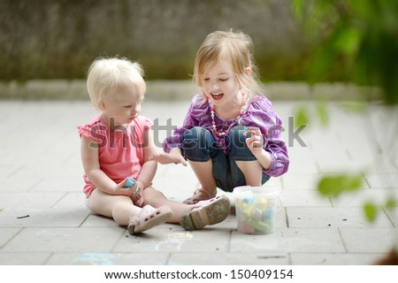 Two sisters drawing with chalk outdoors at summer