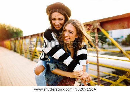 Two sisters having fun outdoor - stock photo