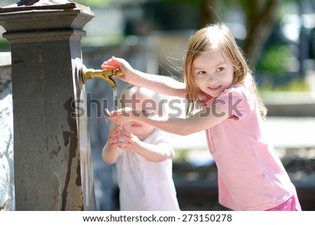 Two sisters having fun with drinking water fountain in Italy - stock photo