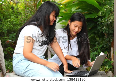 two sisters having fun with laptop in garden