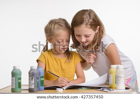 Two sisters help each other while drawing. Pretty children in interest group with talents for painting. Kids look in the album. Paint cans with different colors on the table.