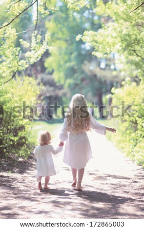 Two sisters holding hands walking in the forest on a summer day