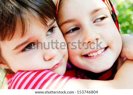 Two sisters hug and squeeze each other - stock photo