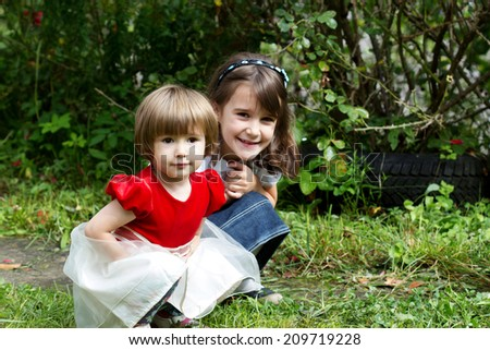 Two sisters hug one another - stock photo