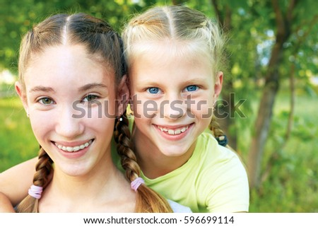 Two sisters hugging and looking at the camera