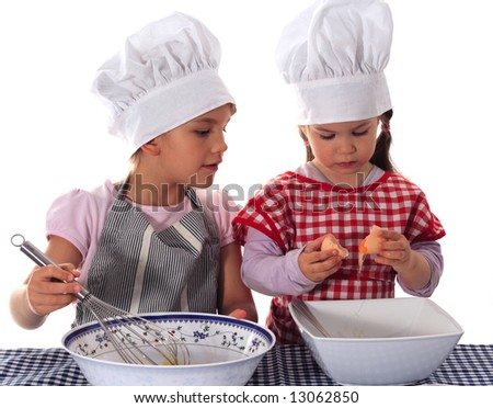 Two sisters in aprons and chef's hats making a cake - stock photo