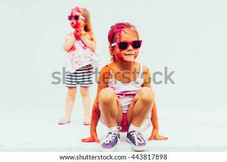 Two sisters in bright colors and cheerful grimy - stock photo