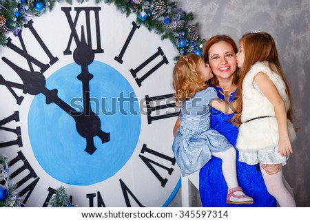Two sisters kiss her mother. Mother keeps child in her arms. The clock in the background show five minutes to midnight. Christmas Eve. New Year. Holiday and fun. Merry Christmas. 2017 - stock photo