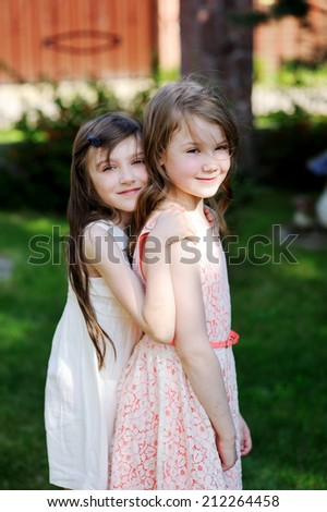 Two sisters laughing and playing in the park - stock photo