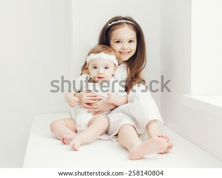 Two sisters little girls in white room at home near window - stock photo