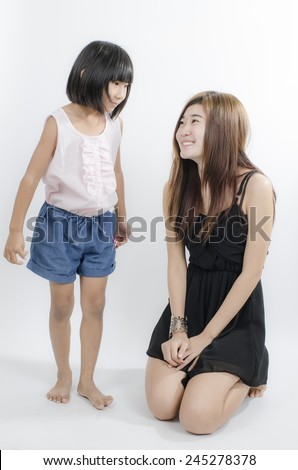 Two sisters looking each other on gray background. - stock photo