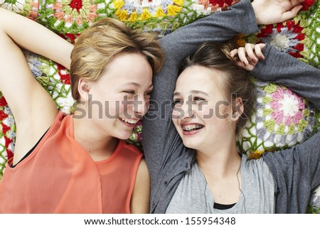 Two sisters lying on a blanket - stock photo