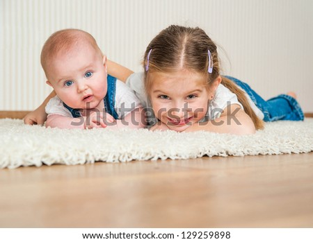 two sisters lying on the floor at home - stock photo