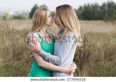 Two sisters or female friends in an intimate embrace standing close together looking deeply into each other eyes - stock photo