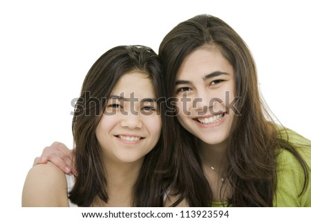 Two sisters or friends hugging each other, isolated on white
