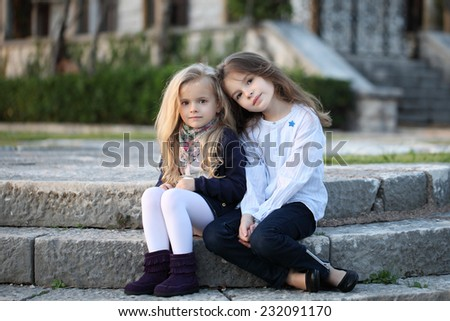 Two sisters outdoors. Children playing in the park. Beautiful girls. - stock photo