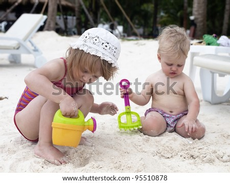 Two sisters play with sand. Koh Lipe island, Thailand - stock photo