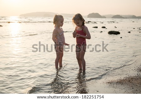 Two sisters playing in water at the beach - stock photo