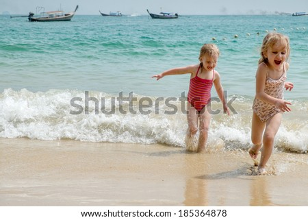 Two sisters playing in water at the beach
