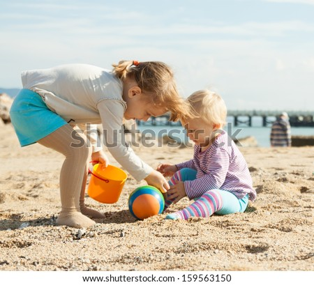 two sisters playing on  beach