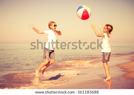 Two sisters playing on the beach at the day time. Concept of friendly sister. - stock photo