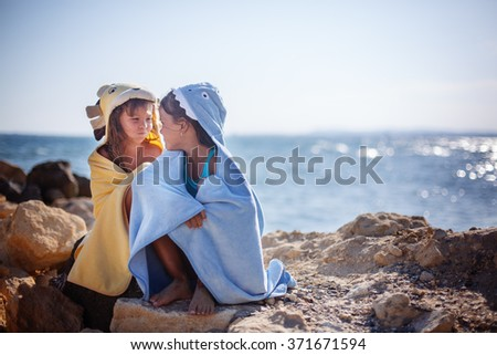 Two sisters playing on the beach, beach towels , sea, sun, warmth and comfort . - stock photo