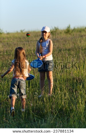 Two sisters playing tennis on the lawn in evening light - stock photo