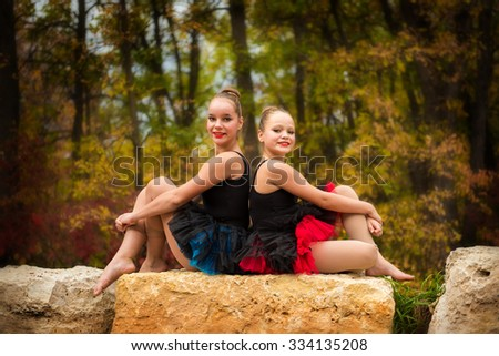 Two Sisters Pose back to back in ballet tutus on a rock in the park in Autumn - stock photo