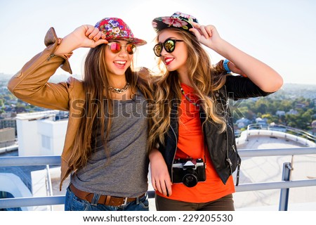 Two sisters posing on the roof, wearing stylish leather jackets swag hats and sunglasses, holding retro camera, ready for shooting, positive emotions. fashion portrait of best friends girls. - stock photo