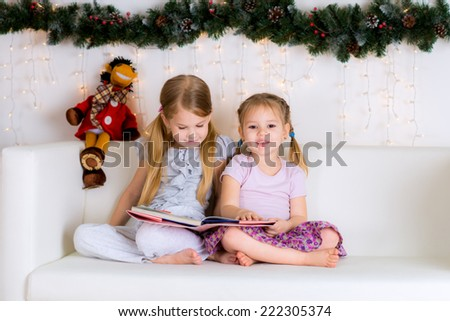 two sisters reading a book in the Christmas decorations near a Christmas tree on a white sofa at home