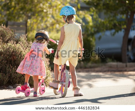 Two sisters riding their bikes together - stock photo