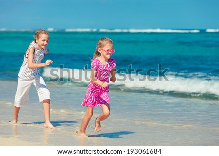 two sisters running on the beach in the day time