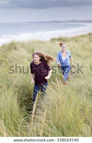 Two sisters running through long grass with the background of the beach. They are wearing casual clothing and smiling.  - stock photo