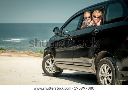 two sisters sitting in a car on the beach - stock photo