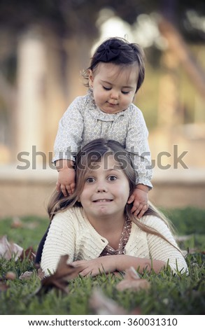 two sisters sitting in a garden in the fal - stock photo