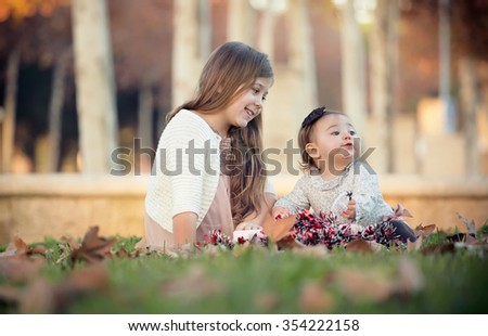 two sisters sitting in a park in the middle of Christmas - stock photo