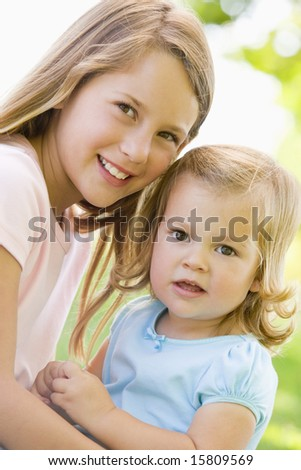 Two sisters sitting outdoors smiling - stock photo