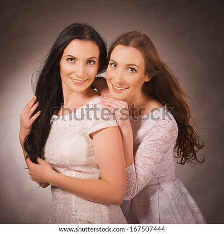 Two sisters smiling and hugging - stock photo