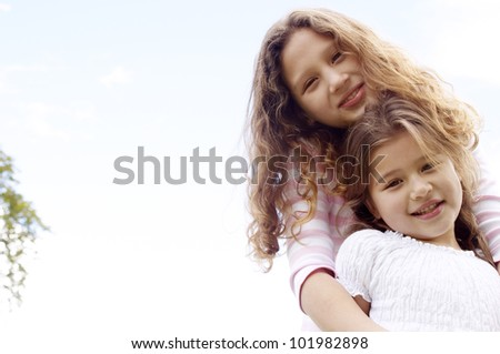 Two sisters smiling for a portrait against a blue sky. - stock photo