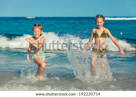 two sisters splashing on the beach in the day time