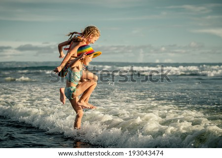 two sisters splashing on the beach in the day time - stock photo