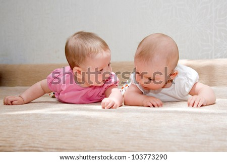 Two sisters, twin baby girls talking and lying on the sofa together - stock photo