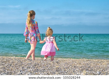 Two sisters walk along the beach - stock photo