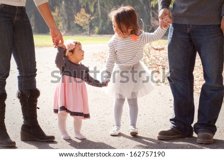 Two sisters walking down a path looking up at each other - stock photo