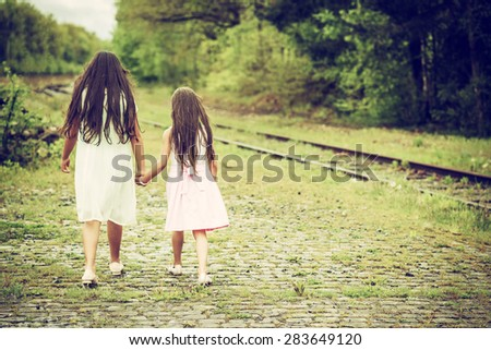 two sisters walking next to railroad track, shot from behind
