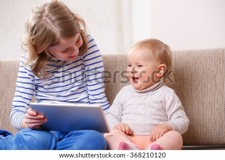 Two sisters watching tablet PC - stock photo