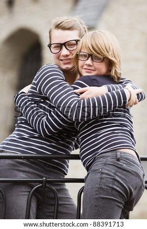 Two sisters wearing fashionable eyeglasses with retro frames, embracing - stock photo