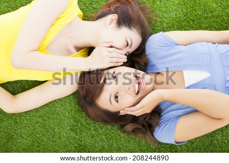 two sisters  whispering gossip on the grass - stock photo