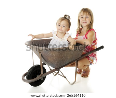 Two sisters with a wheelbarrow -- the baby riding inside, the elementary sister happily squatting behind.  On a white background.