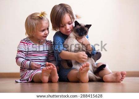 Two  sisters  with cat sitting on the floor indoor - stock photo